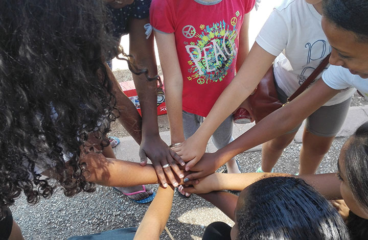 circle of children with hands in center