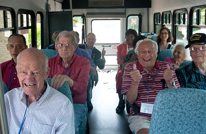 senior citizens cheering on bus