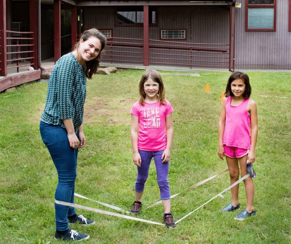 female shlicha (emissary) playing outside with two girl